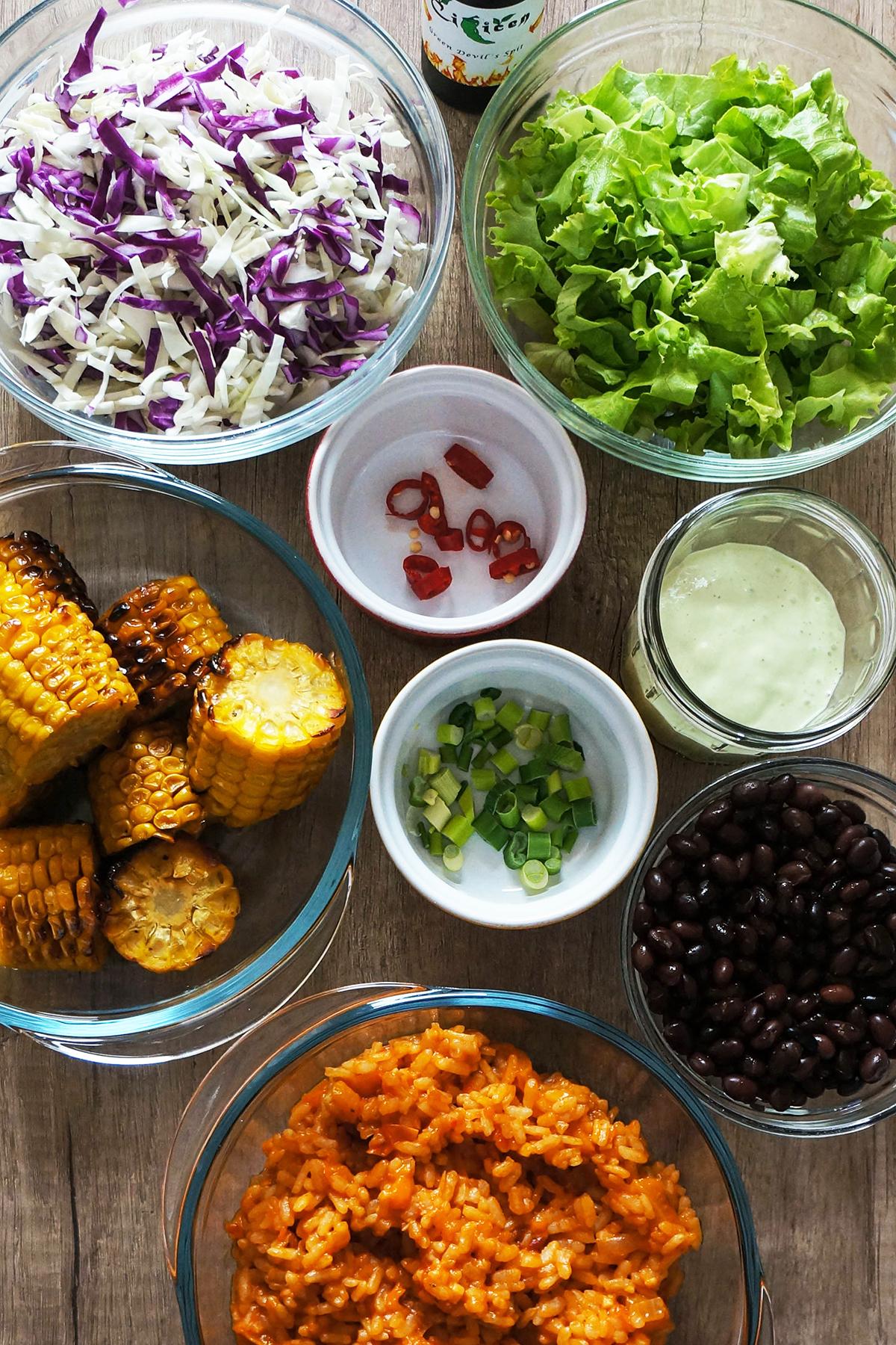 Mehiška pojedina z rdečim rižem, črnim fižolom, zelenjavo in avokadovim prelivom