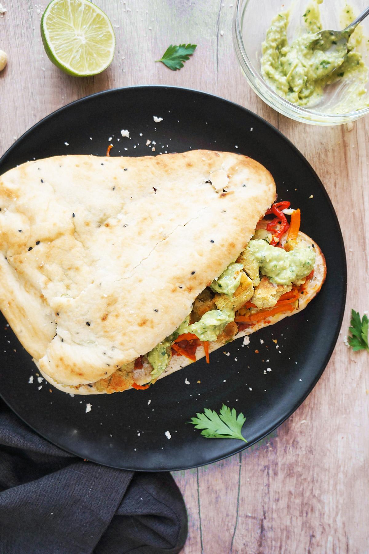 Naan sendvič s falafli, pečeno zelenjavo in avokadovim prelivom