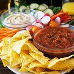 Party krožnik s tortilija čipsom, zelenjavo, paradižnikovo salso in humusom